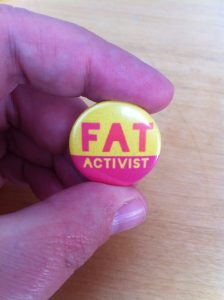 A badge saying Fat Activist pinched between a finger and a thumb