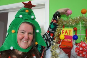 Charlotte Cooper wears a Christmas tree hat and stands proudly in front of her books