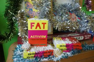 Copies of Fat Activism covered in fake snow and adorned with tinsel